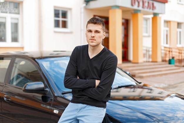 Przystojny stylowy mężczyzna w czarnej koszuli i niebieskich spodniach w pobliżu samochodu