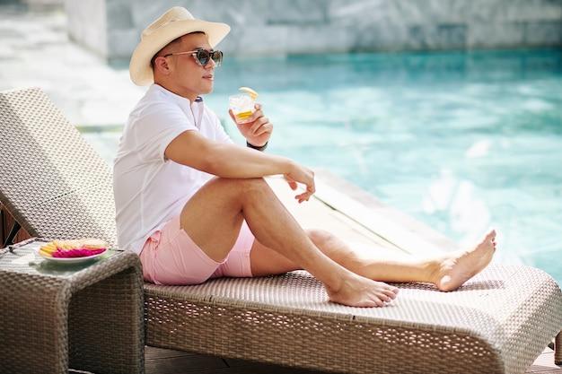 Przystojny stylowy mężczyzna w kapeluszu i okularach przeciwsłonecznych siedzi na szezlongu przy basenie i pije dżin z tonikiem ze skórką pomarańczową