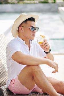 Przystojny stylowy mężczyzna w okularach przeciwsłonecznych i słomkowym kapeluszu, pijący staromodny koktajl i patrzący na hotelowy basen