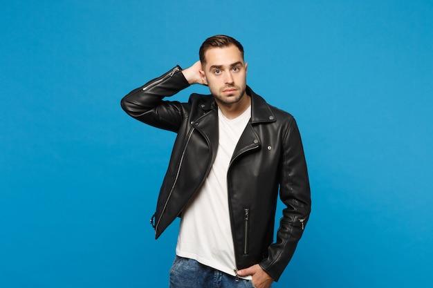 Przystojny stylowy młody brodaty mężczyzna w czarnej skórzanej kurtce biały t-shirt patrząc kamery na białym tle na tle niebieskiej ściany portret studio. koncepcja życia szczere emocje ludzi. makieta miejsca na kopię.