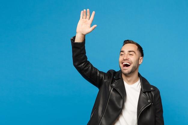 Przystojny stylowy młody człowiek w czarnej kurtce biały t-shirt macha i pozdrowienie ręką, jak zauważa ktoś na białym tle na tle niebieskiej ściany portret studio. koncepcja życia ludzi. makieta miejsca na kopię