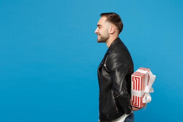 Przystojny stylowy młody mężczyzna nieogolony w czarną skórzaną kurtkę biały t-shirt przytrzymaj pudełko na białym tle na tle niebieskiej ściany portret studio. koncepcja życia szczere emocje ludzi. makieta miejsca na kopię.
