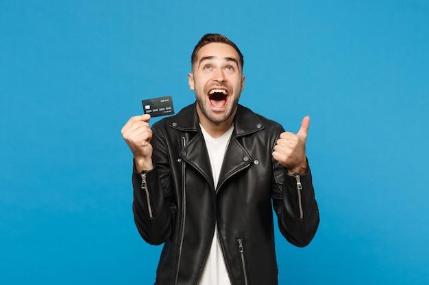 Przystojny stylowy młody mężczyzna nieogolony w czarną skórzaną kurtkę biały t-shirt trzymać w ręku karty kredytowej banku na białym tle na tle niebieskiej ściany portret studio. koncepcja życia ludzi. makieta miejsca na kopię.