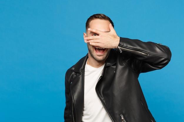 Przystojny stylowy młody nieogolony mężczyzna w czarnej skórzanej kurtce biały t-shirt patrząc aparat na białym tle na tle niebieskiej ściany portret studio. koncepcja życia szczere emocje ludzi. makieta miejsca na kopię
