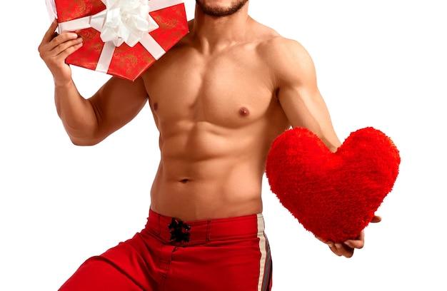 Przystojny święty mikołaj trzymający serce i prezent