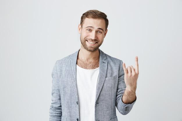 Przystojny szczęśliwy brodaty mężczyzna pokazuje rock-n-roll gest