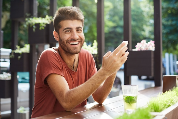 Przystojny szczęśliwy facet siedzi w kawiarni, pije lemoniadę i używa telefonu komórkowego, śmiejąc się z wiadomości tekstowej