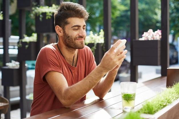 Przystojny szczęśliwy facet siedzi w kawiarni, pije lemoniadę i używa telefonu komórkowego, wiadomości sms