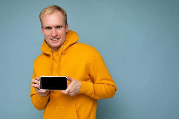 Przystojny szczęśliwy fajny młody człowiek dobrze wyglądający ubrany dorywczo stylowe ubrania stojący na białym tle nad kolorowym tle ściany trzymając smartfon i pokazując telefon z pustym ekranem, patrząc na kamerę
