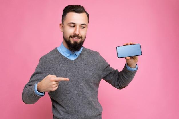 Przystojny szczęśliwy fajny młody nieogolony brunetka mężczyzna z beardwearing stylowy szary sweter i niebieski