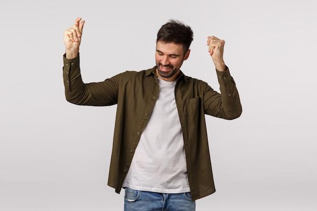 Przystojny, szczęśliwy i odnoszący sukcesy młody człowiek osiąga cel, podnosi ręce i tańczy z radością, triumfuje pompa pięściowa, uśmiecha się wesoły, czuje się szczęśliwy, osiągając cel, podekscytowany świętować zwycięstwo