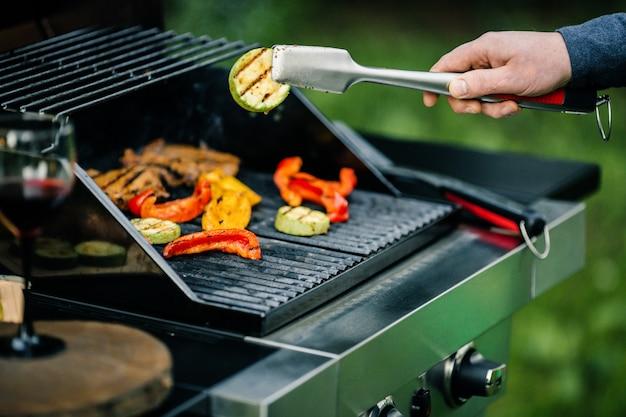 Przystojny szczęśliwy męski narządzanie grill outdoors dla przyjaciół