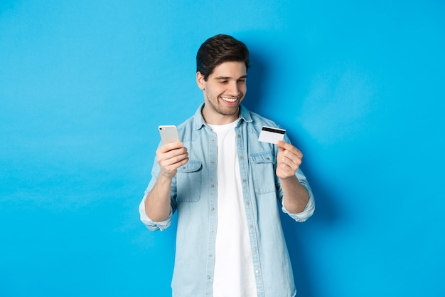 Przystojny szczęśliwy mężczyzna płacący za coś online, trzymając kartę kredytową i telefon komórkowy, zakup w internecie, stojąc na niebieskim tle.