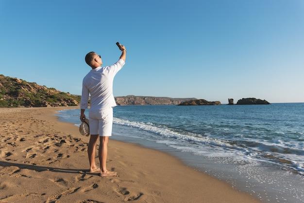 Przystojny szczęśliwy mężczyzna w białej koszuli, biorąc selfie na plaży.