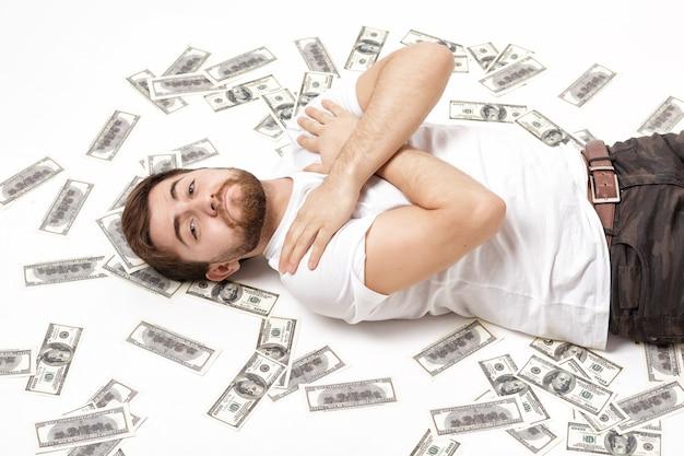 Przystojny szczęśliwy mężczyzna z brodą w białej koszuli leżący na sto