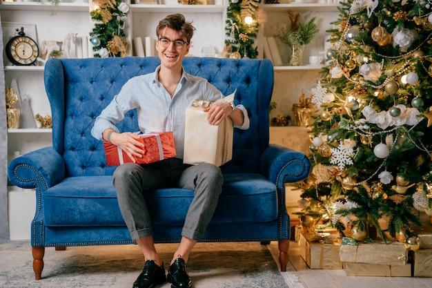 Przystojny szczęśliwy mężczyzna z uśmiechniętym twarzy obsiadaniem na kanapie z giftboxes na jego nogach w pokoju z cristmas drzewem