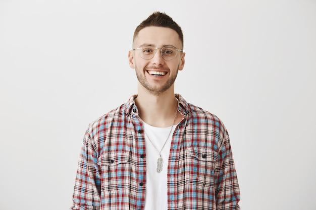 Przystojny szczęśliwy młody chłopak w okularach pozowanie
