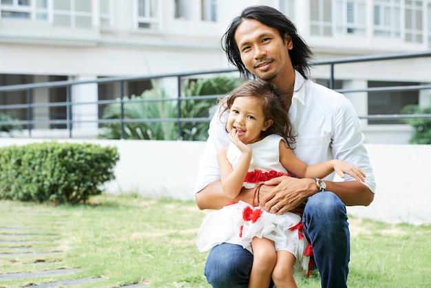 Przystojny szczęśliwy młody człowiek przytulający swoją córeczkę, gdy spędzają niedzielę na świeżym powietrzu