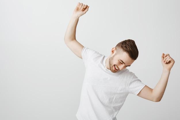 Przystojny szczęśliwy młody człowiek tańczy w białej koszulce na szarej ścianie