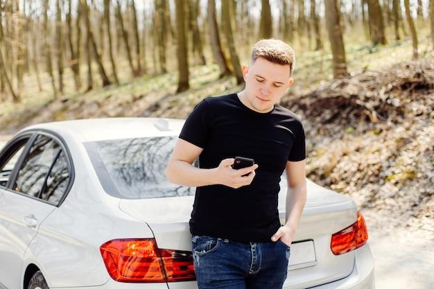 Przystojny, szczęśliwy, młody człowiek używa smartfona w samochodzie i na zewnątrz