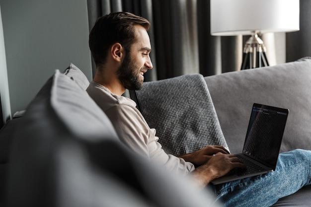 Przystojny szczęśliwy pozytywny młody człowiek pomieszczeniu w domu na kanapie przy użyciu komputera przenośnego.