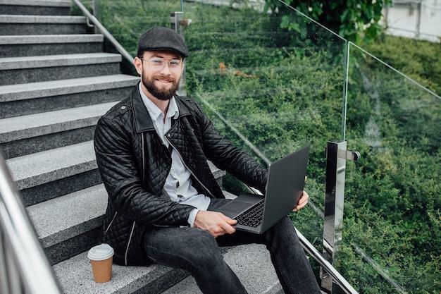 Przystojny szczęśliwy pracownik pije kawę i pracuje na laptopie, siedząc na zewnątrz na schodach