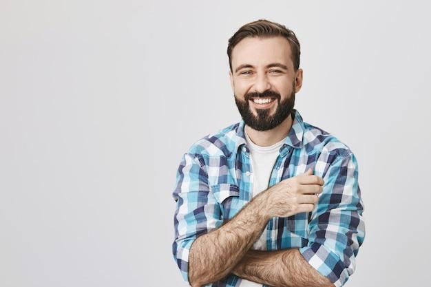 Przystojny szczęśliwy uśmiechnięty mężczyzna z brodą, śmiejąc się