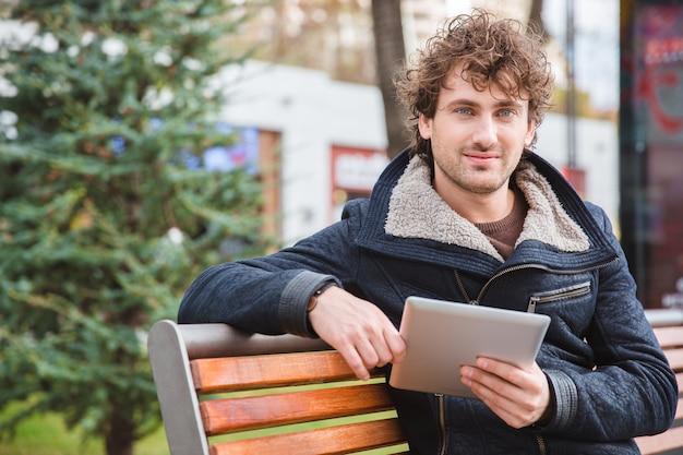 Przystojny szczęśliwy wesoły atrakcyjny zadowolony młody człowiek siedzący na drewnianej ławce w parku i trzymający tablet