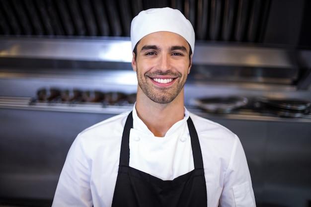 Przystojny szef kuchni patrzeje kamerę