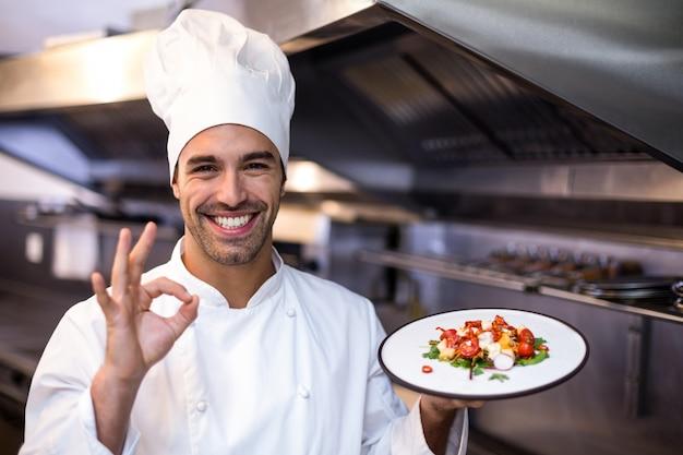 Przystojny szef kuchni pokazuje ok znaka i posiłek