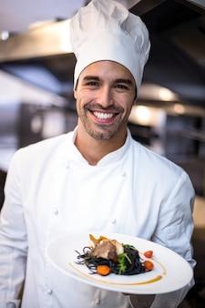 Przystojny szef kuchni przedstawia posiłek