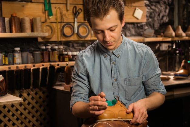 Przystojny szewc siedzi w warsztacie robi buty
