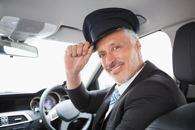 Przystojny szofer ono uśmiecha się przy kamerą