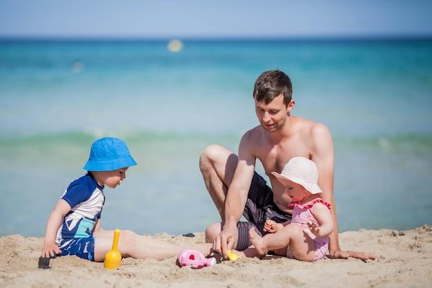 Przystojny tata bawi się z dziećmi w pobliżu morza.