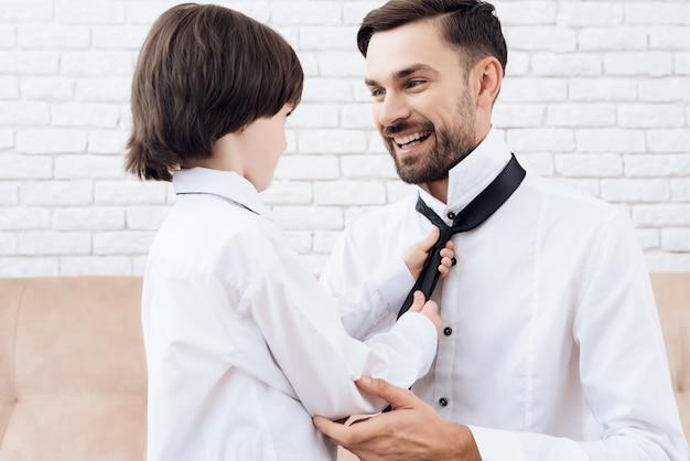 Przystojny tata i syn w tych samych ubraniach.