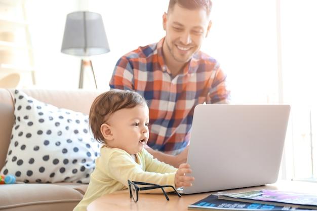 Przystojny tata z synem korzysta z laptopa w domu