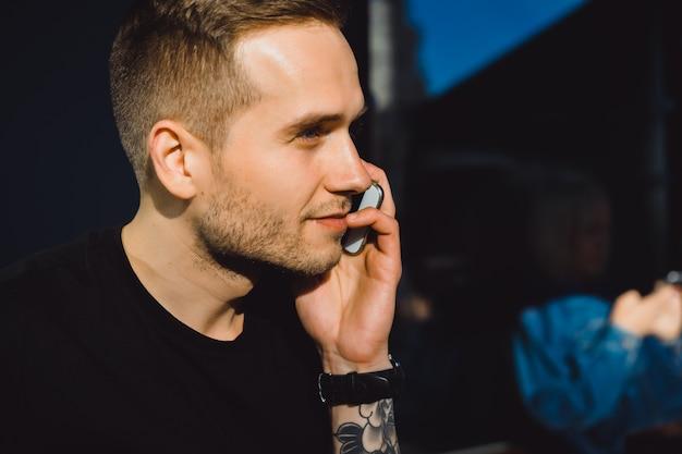 Przystojny tatuaż młody mężczyzna rozmawia przez telefon, portret szczegółom, na zewnątrz pomieszczeń