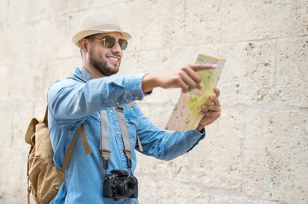 Przystojny turysta mężczyzna patrzy na mapę, wskazując palcem w kierunku celu podróży koncepc...