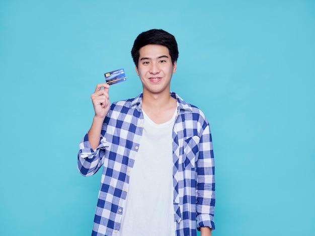 Przystojny turysta mężczyzna z kartą kredytową na jasnoniebieskiej ścianie. koncepcja podróży latem