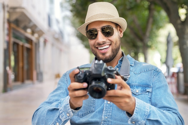 Przystojny turysta sprawdzający zdjęcia w aparacie cyfrowym