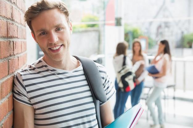 Przystojny uczeń uśmiecha się i trzymając notesy