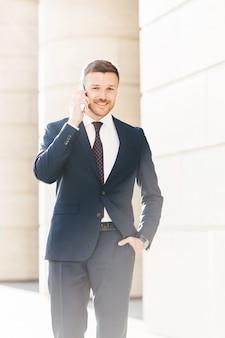 Przystojny udany mężczyzna dyrektor finansowy rozwiązuje problemy za pomocą smartfona