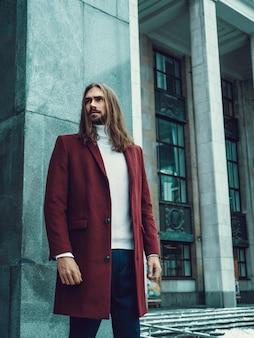Przystojny ufny dobrze ubierający mężczyzna z brodą pozuje outdoors patrzeć daleko od. modny bogaty model męski w czerwonym płaszczu zimowym i białym swetrze