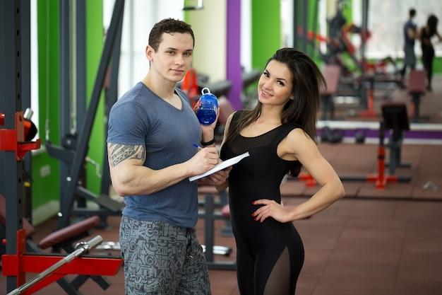 Przystojny umięśniony trener płci męskiej konsultuje atrakcyjną młodą kobietę w siłowni zarówno uśmiechnięty
