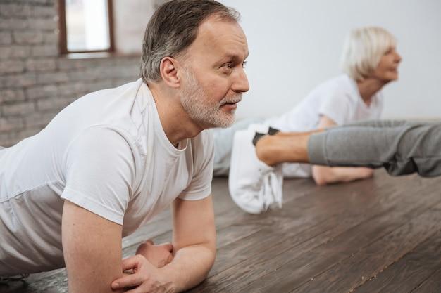 Przystojny, uprzejmy brodaty mężczyzna ubrany w białą koszulkę, opierając ramiona na podłodze, patrząc prosto