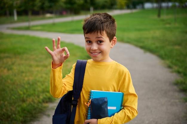 Przystojny, uroczy uczeń pokazujący singn ok ręką, stojący z plecakiem i przyborami szkolnymi w parku miejskim