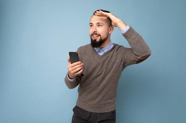 Przystojny uśmiechający się brunetka brodaty mężczyzna ubrany w szary sweter i niebieską koszulę na białym tle na tle ściany trzymając telefon komórkowy, patrząc z boku.