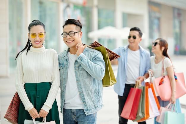 Przystojny uśmiechnięta młoda kobieta przytulanie swoją dziewczynę, gdy stoją na zewnątrz po zakupach razem