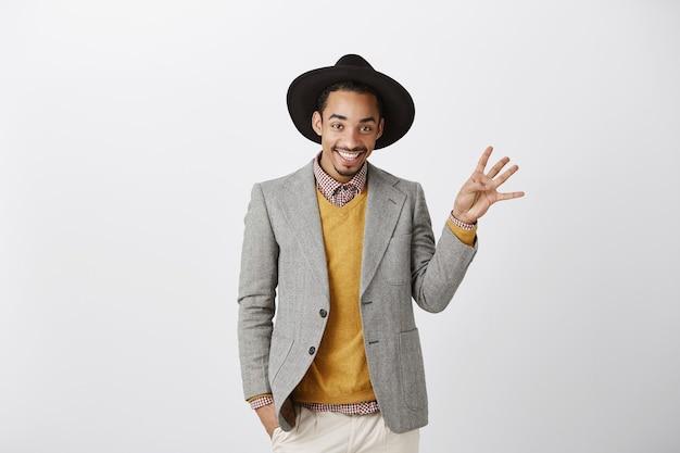 Przystojny uśmiechnięty afroamerykanin w stylowym garniturze pokazując numer cztery, porządkując