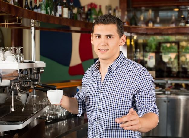 Przystojny uśmiechnięty barista trzyma filiżankę kawy i wskazuje palec.